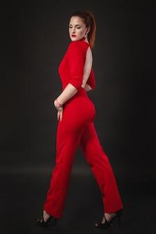 笑顔の女性の肖像画。赤いオーバーオールを着ている女の子