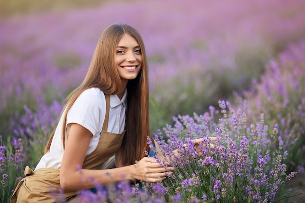 ラベンダー畑でポーズをとって笑顔の女性