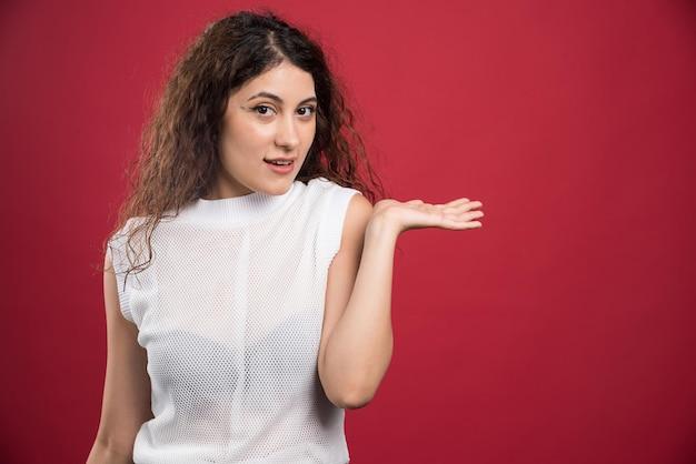 Улыбающаяся женщина позирует на красном
