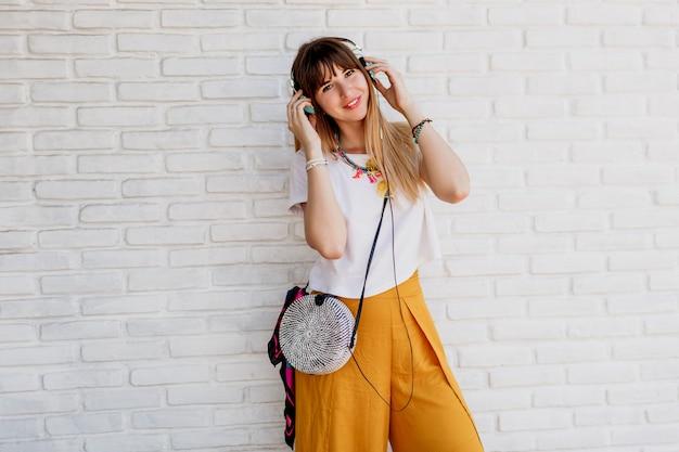 Улыбающаяся женщина позирует над белой кирпичной стеной с наушниками и показывает знаки.