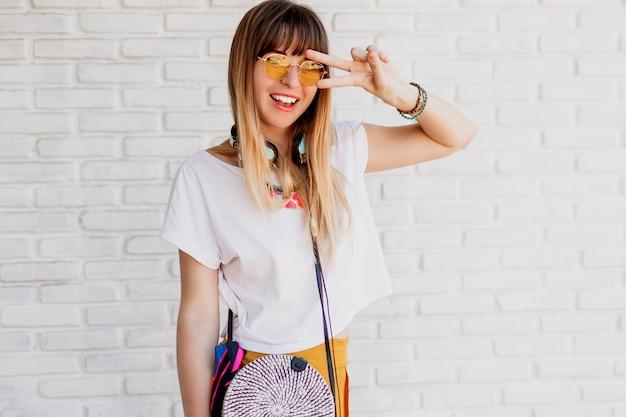イヤホンで白いレンガの壁を越えてポーズと兆しを見せて笑顔の女性。