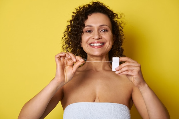 デンタルフロスを手にカメラに向かってポーズをとる笑顔の女性。口腔および歯科治療の概念