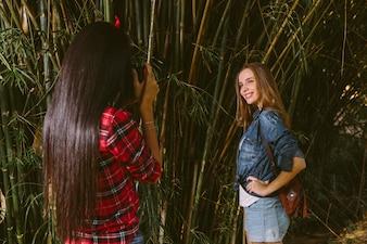 カメラで写真を撮っている彼女の友人の間に笑っている女性