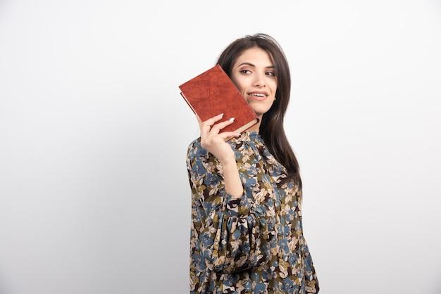 本でポーズをとって笑顔の女性。