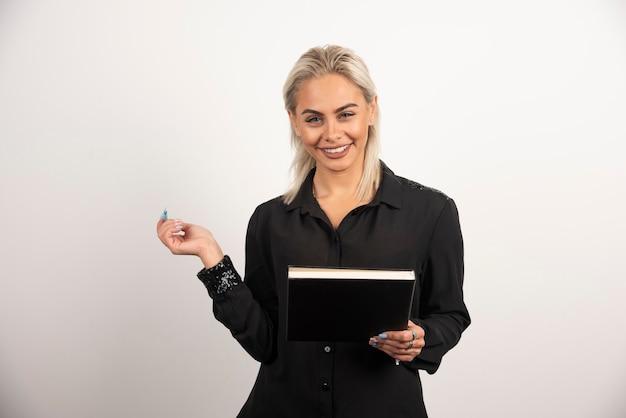 Donna sorridente in posa con una tazza e appunti su sfondo bianco. foto di alta qualità