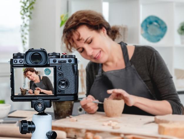 Улыбается женщина-гончар, работающая с продуктом в мастерской. профессия блоггера