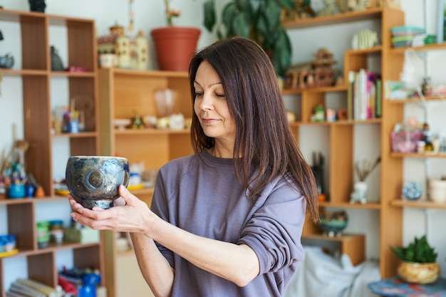 Smiling woman potter in the workshop holding clay bowl. the master shows her work.