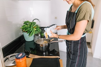 Smiling woman pouring rigatoni pasta in the sauce pan over the electric stove