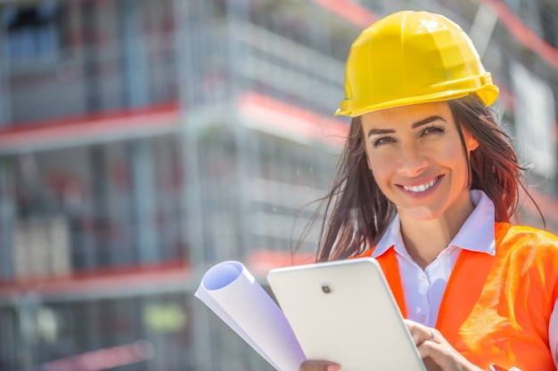 Smiling woman in ppe holds a tablet and a blueprint with a construction site in the background.