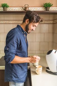 キッチンでコーヒーを準備する笑顔の女性