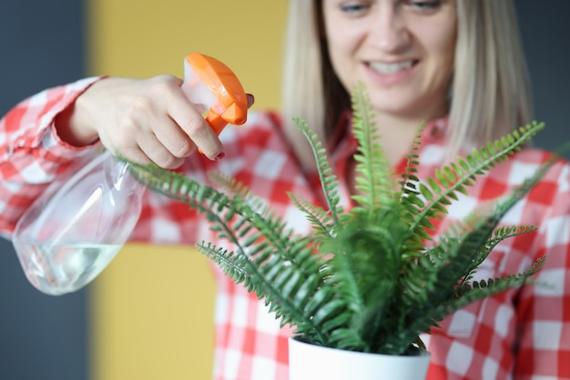 Smiling woman processes a flower in flowerpot. home plant growing concept