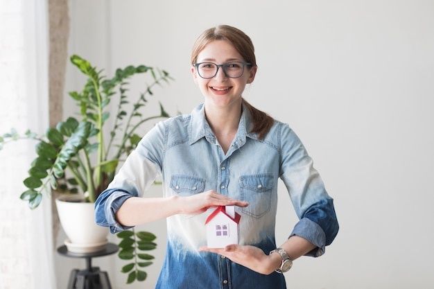 Smiling woman protecting house model at office looking at camera