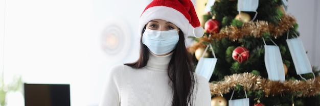 Smiling woman in protective medical mask stands next to christmas tree and holds gift.