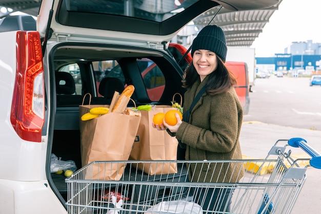笑顔の女性が食料品店のコピースペースの後に車のトランクに製品のバッグを入れました