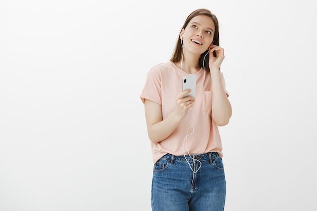 웃는 여자는 휴대 전화 앱에서 팟 캐스트를 듣기 위해 이어폰을 넣어