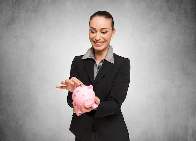 笑顔の女性は彼女の貯金箱にお金を入れて