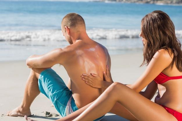 Smiling woman putting sun cream on her boyfriends back