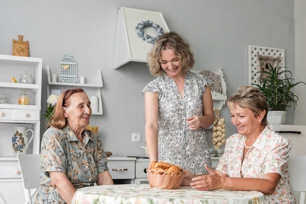 Smiling woman putting wicker basket of croissant on table in front of mature woman and senior woman