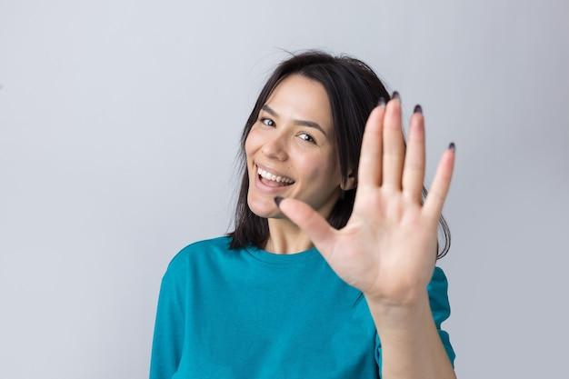 웃는 여자는 손을 흔드는 것처럼 손바닥을 위아래로 올렸다.