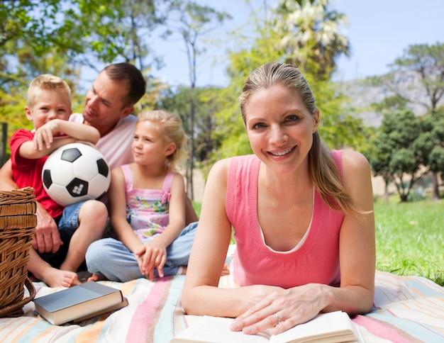 彼女の家族とピクニックで読書をする笑顔の女性