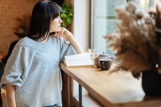 커피숍에서 웃는 여자 읽기 책. 카페 테이블에 앉아서 책을 읽는 젊은 예쁜 여성의 사진.