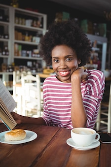 Smiling woman reading a book in cafe