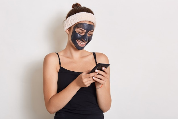Smiling woman reading message on smart phone with black mask on her face, wearing hair band and sleeveless t shirt