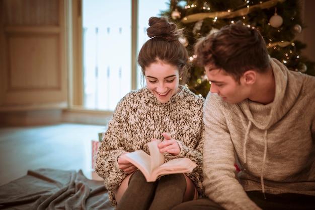 Smiling woman reading novel at boyfriend