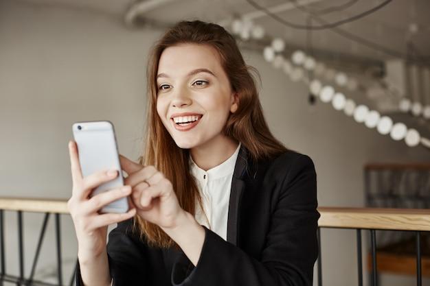 笑顔の女性は幸せな携帯電話を見て、楽しいメッセージを受け取ります