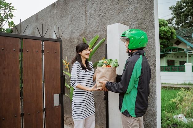 Улыбающаяся женщина, получающая доставку продуктов на дом