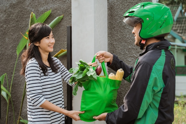 Smiling woman receiving grocery delivery at home