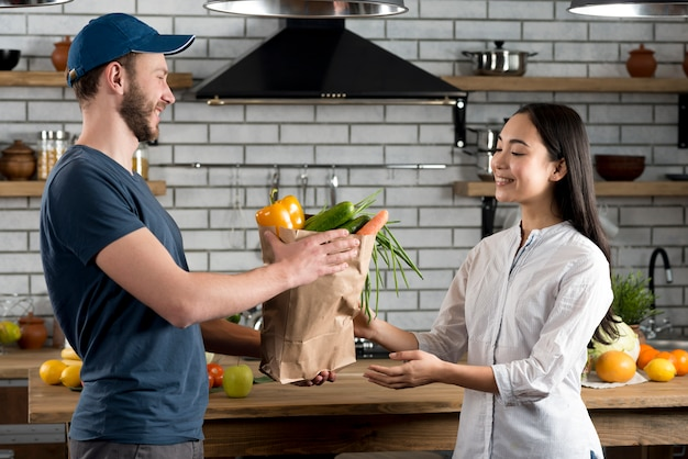 Smiling woman receiving grocery from delivery man in kitchen
