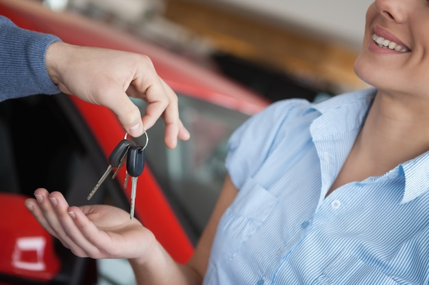 Smiling woman receiving keys from somebody