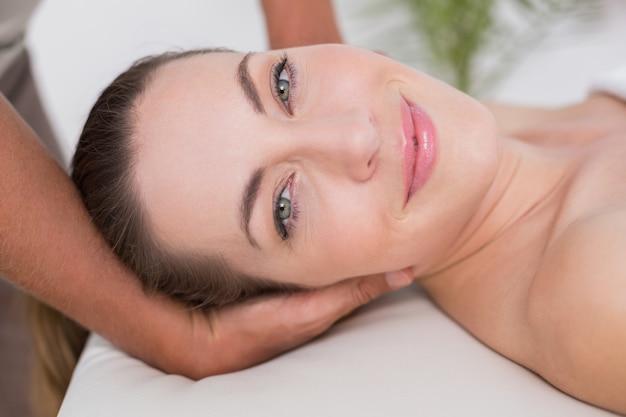 Улыбка женщины, принимающей массаж шеи