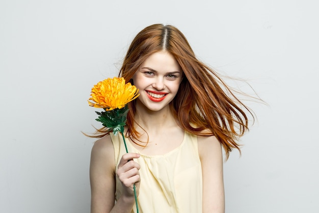 チャームギフトモデルの手に笑顔の女性赤い唇黄色い花。高品質の写真