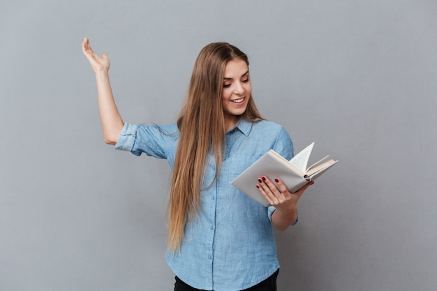 Smiling woman rehearses with book in hand