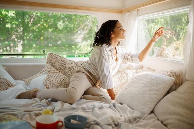 웃는 여자는 트레일러에서 캠핑, 침대에서 휴식. 커플은 밴, 캠핑카 휴가, 캠핑카 캠핑 레저