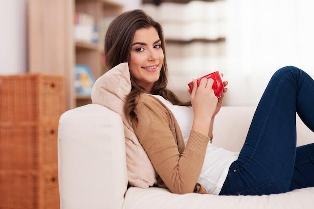 一杯のコーヒーと一緒に家でリラックスして笑顔の女性