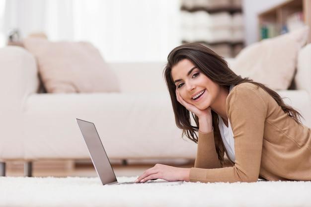 ノートパソコンで家でリラックスして笑顔の女性