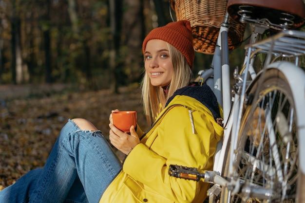 Улыбающаяся женщина расслабляется в осеннем лесу, держа чашку кофе
