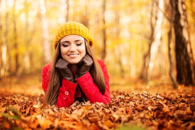 Улыбающаяся женщина отдыхает в парке осенью