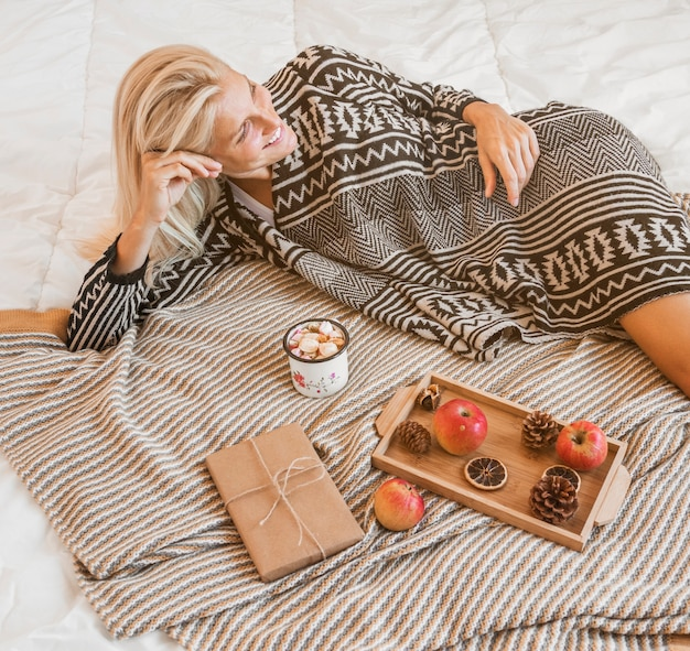 Smiling woman relaxing near hot beverage and gift