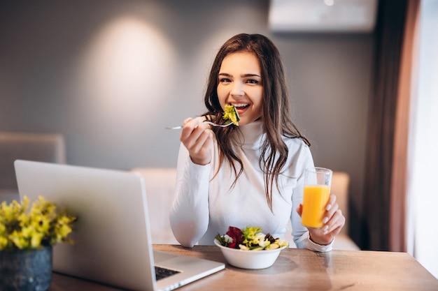 ノートパソコンでリラックスして、キッチンでオレンジジュースを飲みながらポーズをとる笑顔の女性。