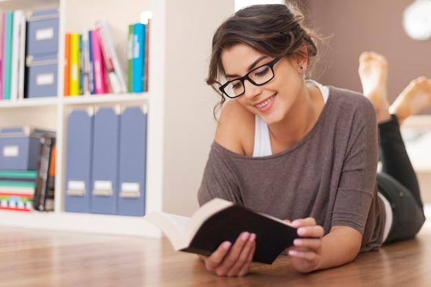 彼女のお気に入りの本でリラックスして笑顔の女性