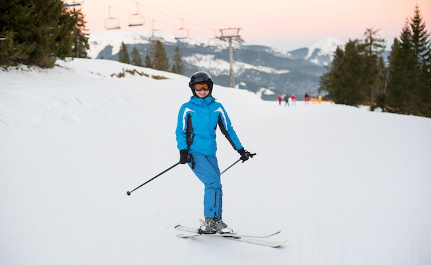 Smiling woman riding skis on the snowy mountain at a winter resort with ski lifts in background.