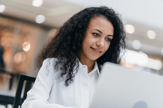 Улыбающаяся женщина ведет свой блог в кафетерии торгового центра