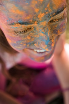 Smiling woman's face with blue and yellow holi powder