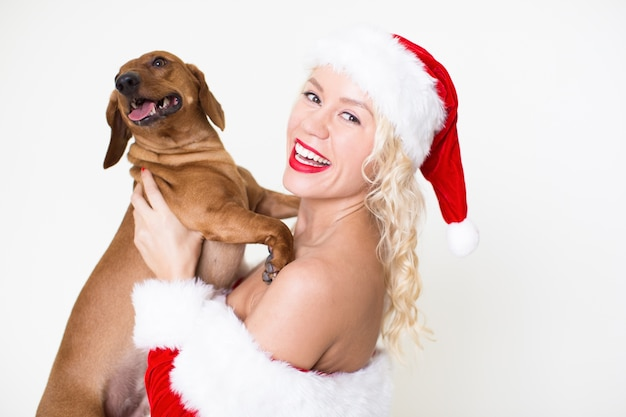 Smiling woman in santa hat holding beloved dog