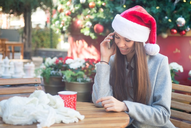 Smiling woman in santa hat talking on her phone in cafe outside