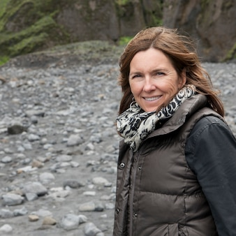 Smiling woman in scarf and vest at rocky dry riverbed before cliff